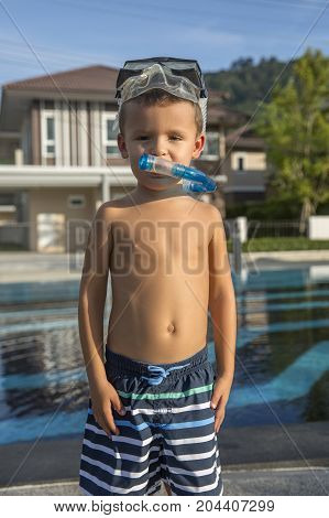 Little boy in a mask for diving on pool background