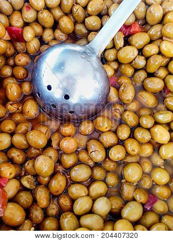 Brown dark green cured olives hot pepper onions in brine with ladle. Shiny glossy texture. Healthy mediterranean diet Spain Italy Israel. Vibrant colors top view