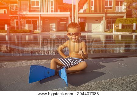 Little boy in a flippers for diving on pool background. Toned