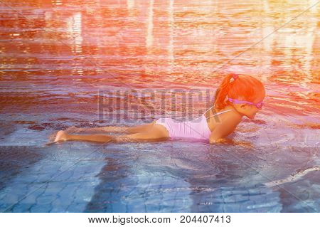 Cute girl with goggles in swimming pool. Toned