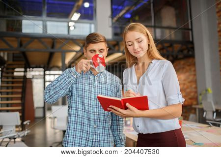 Man with a red cup, girl with a red notebook. Coworkers working together in modern coworking studio. Talking with colleague about new startup project. Horizontal.
