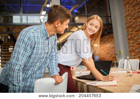 Man and woman working together in modern coworking studio. Talking with colleague about new startup project. Horizontal.