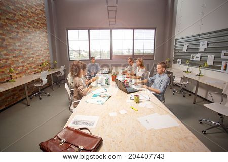 Developing new app. Team of young app developers seriously thinking about their project sitting in a light room.