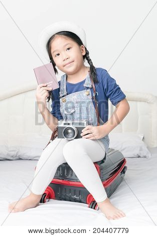 Asian Cute Girl Show Passport And Sit On Suitcase,