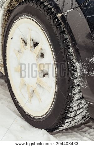 Car wheel with snowy winter tire. Car tyre for winter.
