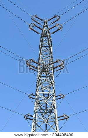 Electricity pylon against blue sky in summer