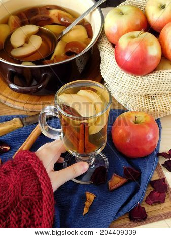Apple compote in an Irish mug. Female hand is holding a glass of warm compote