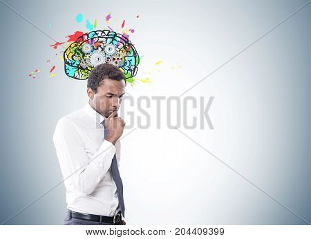 Portrait of a young pensive African American businessman wearing a white shirt and a gray tie. Gray wall background with a colorful brain with gears. Mock up