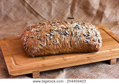 Rye Bread With Pumpkin Seeds On A Wooden Platter On Burlap
