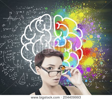 Portrait of a young surprised woman with short red hair taking off her glasses. She is standing near a blackboard with formulas and a colorful brain sketch on it.