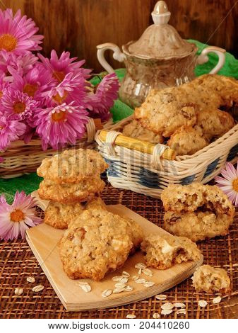 Homemade oatmeal cookies on a wooden board surrounded by pink flowers