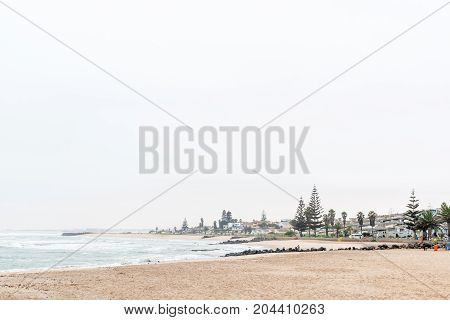 SWAKOPMUND NAMIBIA - JUNE 30 2017: A misty beach scene with holiday apartments in Swakopmund in the Namib Desert on the Atlantic Coast of Namibia