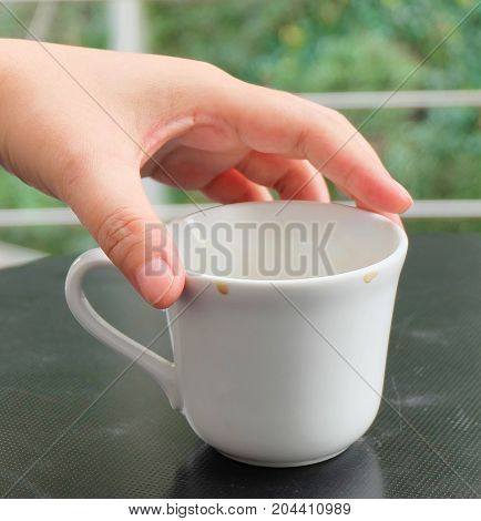 Cuisine and Food Hand Holding An Empty Cup After Drinking Coffee on The Table.