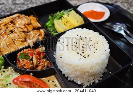 Traditional Japan Cuisine Bento Box or Multi-Layered Box with Teriyaki Chicken Rice Salad Tamagoyaki or Rolled Omelette Hiyashi Wakame or Seaweed Salad and Kimchi Served with Paprika Powder.