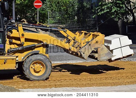 Front end loader works at the road construction