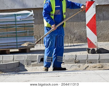 Man is working at the road construction with a shovel