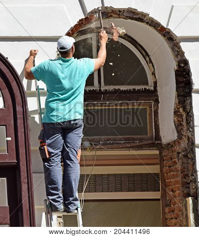 Man is working at the consturction of a building