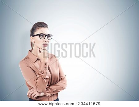 Portrait of a pensive young woman with dark hair wearing glasses and a beige blouse. Gray background. Concept of decision making. Mock up