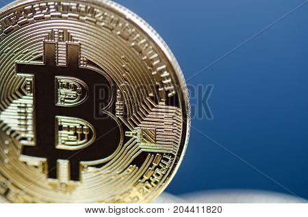 Golden bitcoin coins on a dark background with reflection. Virtual currency. Crypto currency. New virtual money