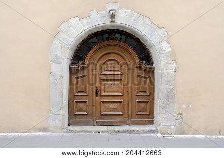 Architectural landmark - Ancient wooden door (gate) with forged arched windows in a building with a beige wall