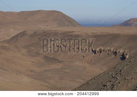 Dry river valley in the Atacama Desert of northern Chile running towards the Pacific Ocean.