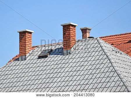 House roof with smoke stacks against sky