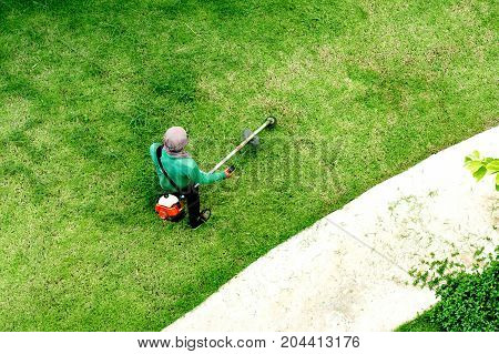 man worker cutting grass with lawn mower