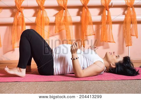 happy 40 week pregnant mid age caucasian woman laying on the mat resting during the yoga class