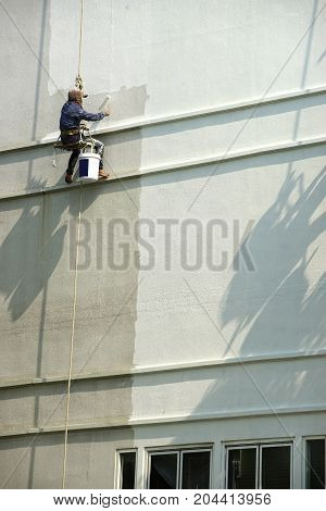 painter hanging on white building , hanging worker