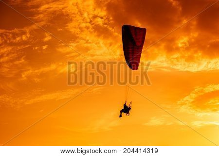 Paramotor flying on the sky at sunset.Paramotor silhouette on the orange sky