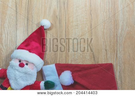 Santa Claus doll with Santa Claus red hat in Christmas day on wooden background with copy space