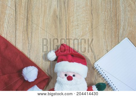 Santa Claus doll with Santa Claus red hat and notebook in Christmas day on wooden background with copy space