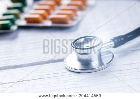 Pharmacy background on a white table. Stethoscope on a white wooden background. Copy space for a text. Tablets on a white background. Pills. Medicine and healthy.