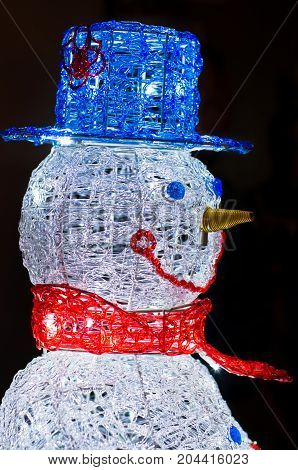 Closeup profile of a Snowman made of led lights with blue hat and red scarf on black background at night