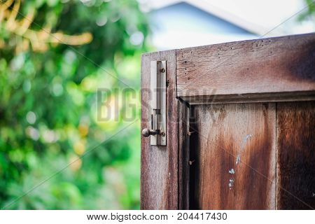 A latch of bar lock at the old wooden window. Protect Anti-theft Protection.