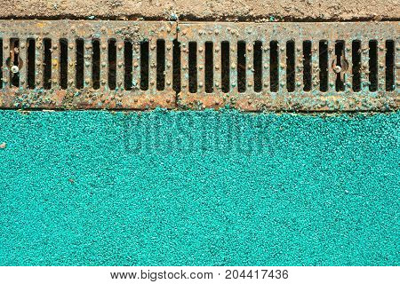 metal gutter on the sidewalk framed by colored asphalt in the cityscape