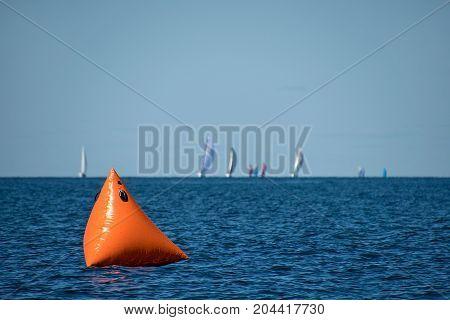 orange sail boat race marker floating on Lake Michigan