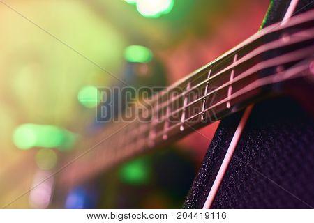 Closeup of guitar fingerboard at concert in light