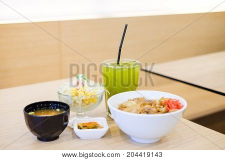 The food set consists of rice with grilled pork teriyaki spring onion & carrot on top white bowl serve with tofu soup (Miso soup) tomato cabbage & corn salad and green tea - japanese food concept.