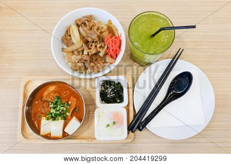 Food set consists of rice with grilled pork teriyaki spring onion & carrot on top bowl serve with tofu & cabbage soup (kimchi) soft boiled egg (onsen) wakame seaweed and green tea - japanese food.