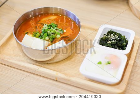 The homemade food set consists of spicy kimchi soup (bacon slice pork white tofu spring onion & cabbage) soft boiled egg (onsen) green seaweed with white sesame serve on wooden tray.