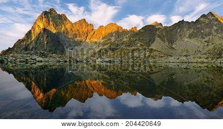 Sunrise in High Tatras in Slovakia. Monumental peak Prostredny hrot. Summer scenic landscape mountain view. Alpine trail. Small cold valley with Prostredne Spisske tarn.