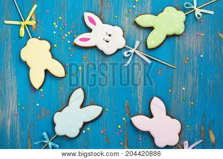 Easter cookies over blue wooden background. Funny bunnies. Space for text