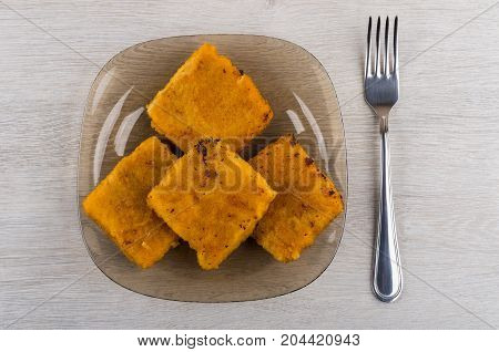 Pieces Of Fish In Breadcrumbs On Plate, Fork On Table