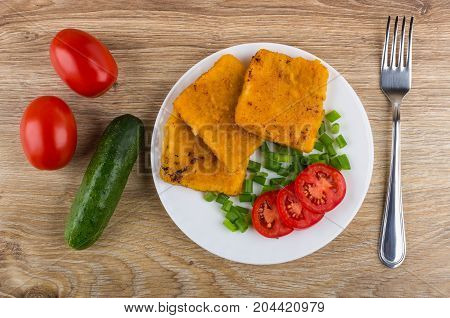 Fish In Breadcrumbs, Tomatoes, Scallion On Plate And Fork