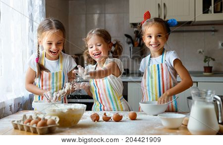 happy sisters children girls bake cookies knead dough play with flour and laugh in the kitchen