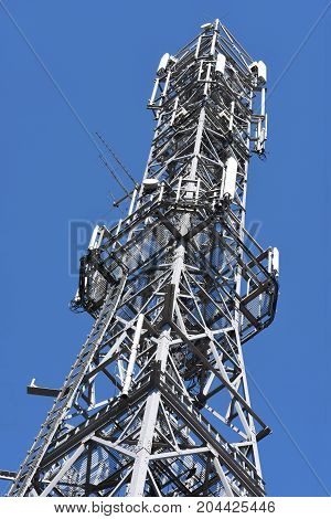 Steel telecommunication tower against clean blue sky