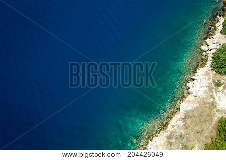 A birds eye view of the Adriatic sea and rocky shore.