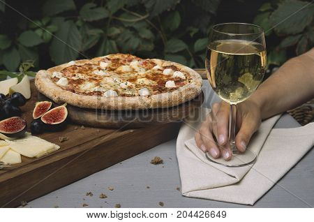 Pizza on board, cheese, bread. Woman hand holds a glass of wine
