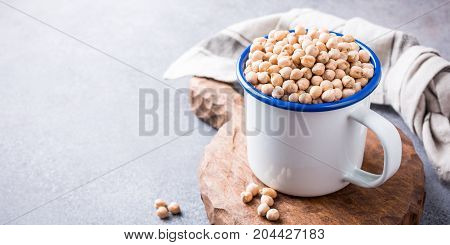Raw uncooked organic chickpeas in white enamel mug on rustic wooden board on light gray stone background. Healthy vegan vegetarian food concept. Banner.